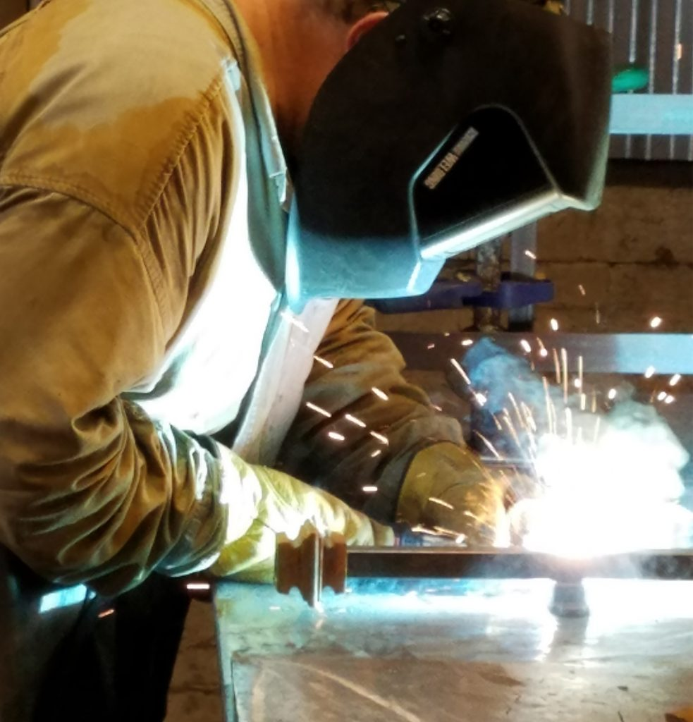 Welder handcrafting custom furniture and lighting design