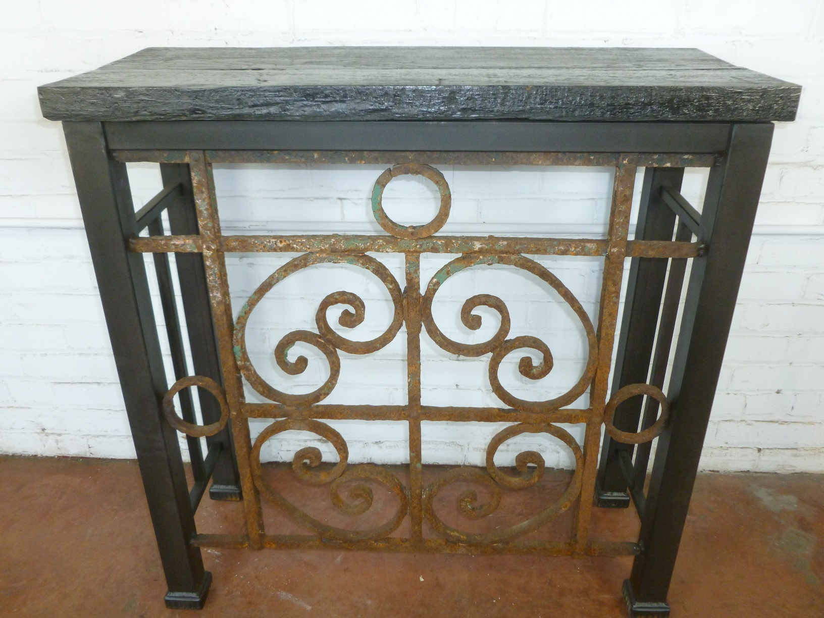 Custom iron console table by Ferro Designs LLC with a barnwood top and a dark iron base finish.