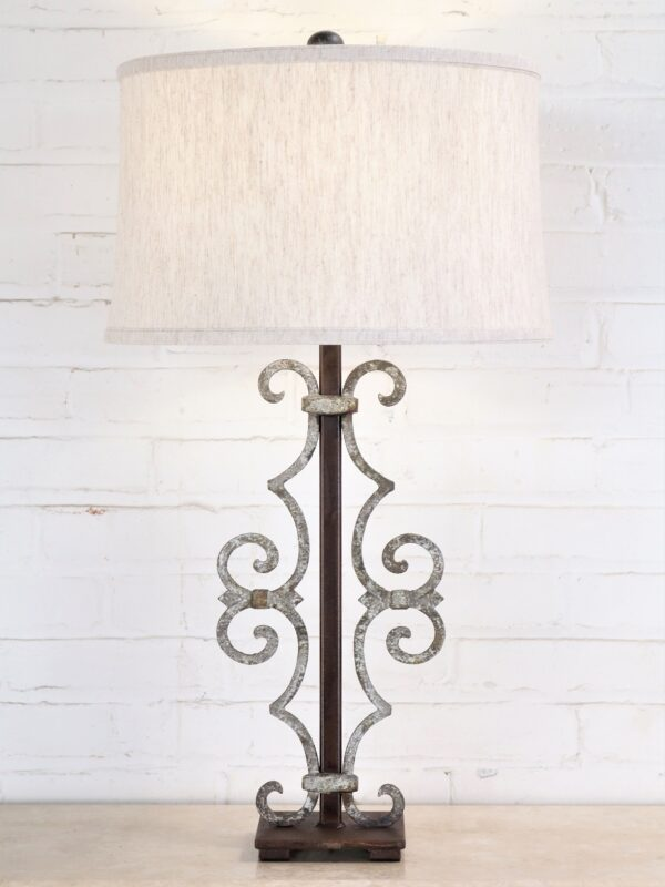 Scroll custom iron table lamp with white, distressed finish on a dark iron base
