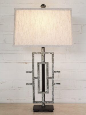 Geometric custom iron table lamp with a gray, distressed finish on a dark iron base. Paired with a 14 inch rectangle linen lamp shade.