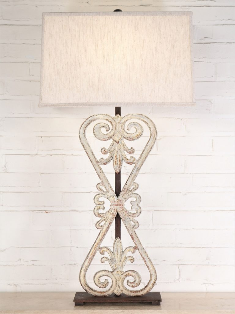Flower bow custom iron table lamp with a white, distressed finish and a dark iron base. Paired with a 19 inch rectangle linen lamp shade.