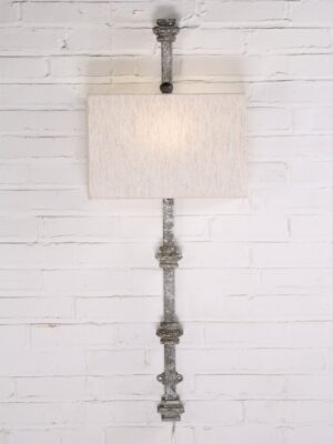 Custom iron wall sconce with a gray, distressed finish and a half rectangle linen lamp shade.