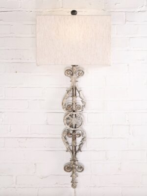Spanish style custom iron wall sconce with a white, distressed finish. Paired with a half rectangle linen lamp shade.