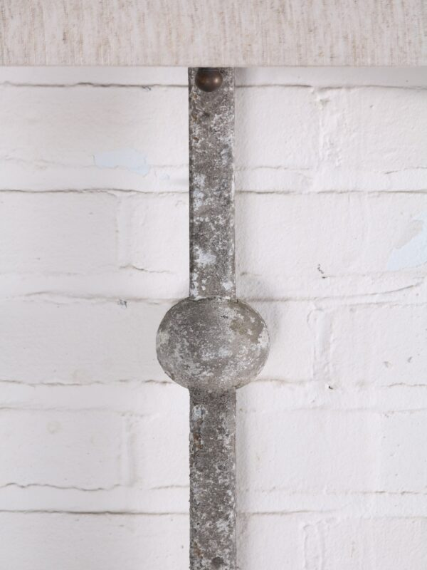 Custom iron wall sconce with a gray, distressed finish.