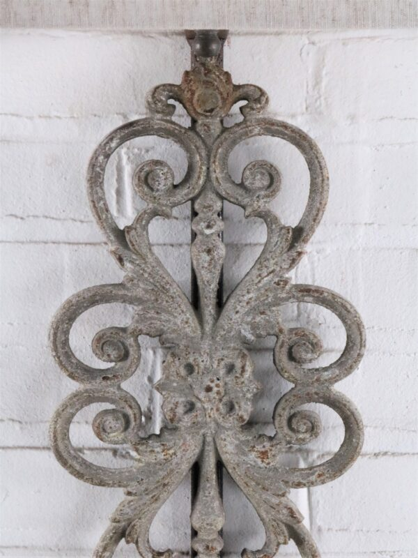 Scrollwork custom iron wall sconce with a gray, distressed finish. Paired with a half rectangle linen lamp shade.