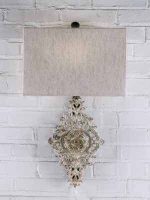 Medallion custom iron wall sconce with a white, distressed finish. Paired with a half rectangle linen lamp shade.