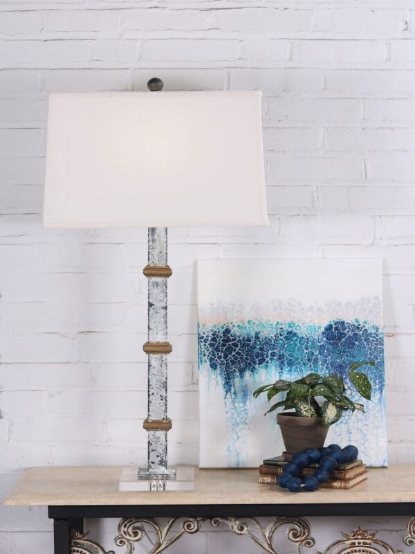 White metal table lamp with gold accents and an acrylic base. Paired with a 17 inch linen lamp shade.